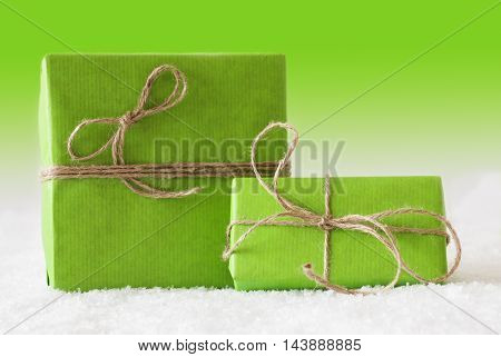 Two Green Christmas Presents On Snow. Card For Birthday Or Seasons Greetings. Natural looking Ribbon. Green Background