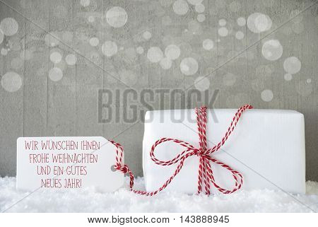 One Christmas Gift Or Present On Snow. Cement Wall As Background With Bokeh. Modern And Urban Style. Label With German Text Frohe Weihnachten Und Ein Gutes Neues Jahr Means Merry Christmas And Happy New Year