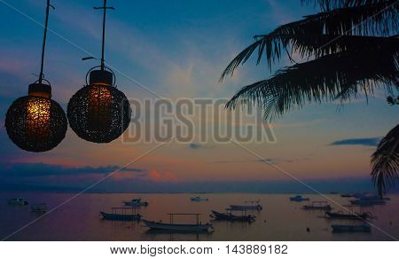 Torches on a sunset background in tropical sea with fishing boats
