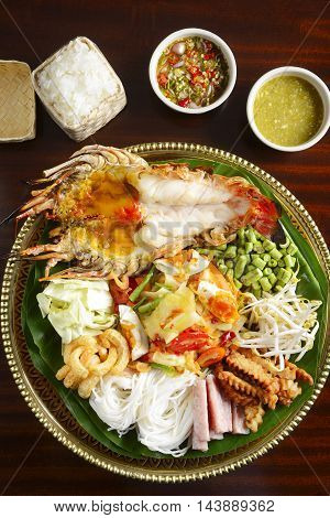 Tray of fried lobster with potatoes vermicelli green bean vegetables rice and chili sauce on green leaf tray in asia