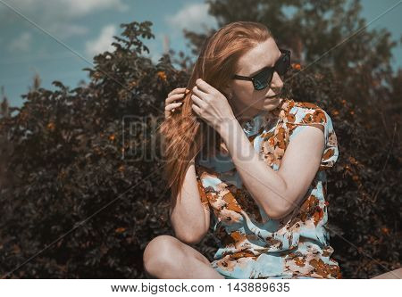 Beautiful redhead girl in the summer day outdoors with sunglasses.