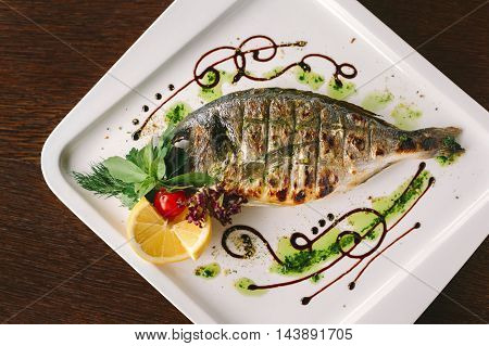 Fried snapper fish with lemon and herbs on white plate