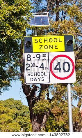 Solar powered School Zone sign on the local road next to footpath