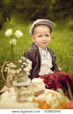 little boy in a jacket and plaid pants to sit on the cushion next to a bouquet of wild flowers the old days a child in a retro style