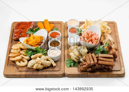 Snacks of fried shrimp squid tempura fish paste potatoes and chicken on wooden cutting board