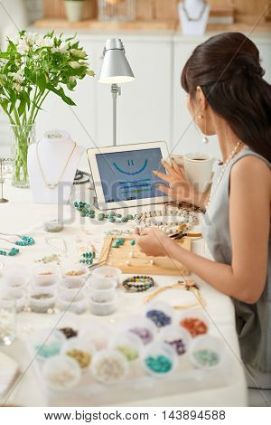 Woman following pattern on tablet computer when making necklace