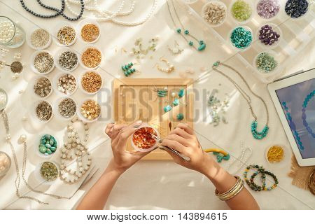 Jewelry designer choosing gems for new work, view from the top