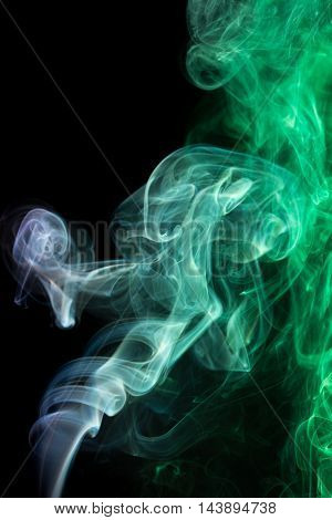 Abstract art. Color purple emerald smoke from the aromatic sticks on a black background. Background for Halloween. Texture fog. Design element. The concept of aromatherapy.