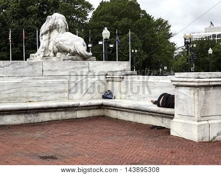 Homeless Peson Sleeping On A Marble Bench