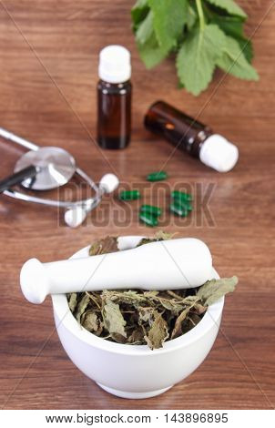 Dried Lemon Balm In Mortar, Stethoscope And Medical Capsules, Choice Between Pills And Alternative M