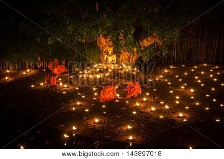 CHIANG MAI THAILAND - JULY 11: Unidentified Thai monks lighting candles to worship the waterfront at Phan Tao temple in Asalha Puja Day on July 11 2014 in Chiang Mai Thailand.