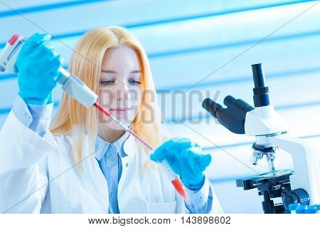 Young woman technician use pipette in laboratory