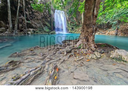 Waterfall landscape background. Beautiful nature outdoor photography. Thailand green rain forest jungle with trees and bushes fresh clean and cool water river flows through stones cascades and roots