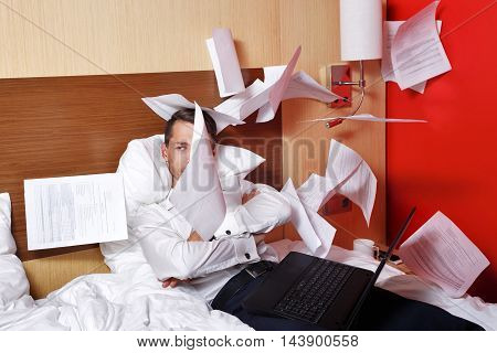 The hell with the job. Businesswoman throws documents. Man with laptop sitting on the couch with his arms crossed and fly papers around him. Deadline. Eff it!