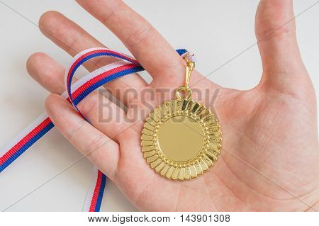 Man is holding golden medal in hand.