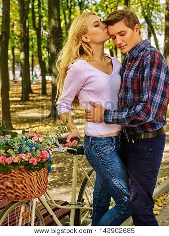 Young couple with flower bicycle in park. Loving couple kissing near white bicycle in autumn park.