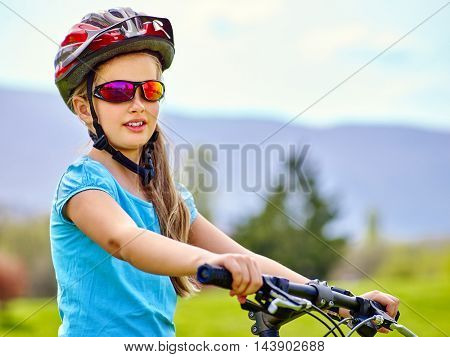 Portrait of girl rides bicycle. Little girl wearing bicycle helmet in cycling. Bicycle look away. Bicycle girl on mountains on background.