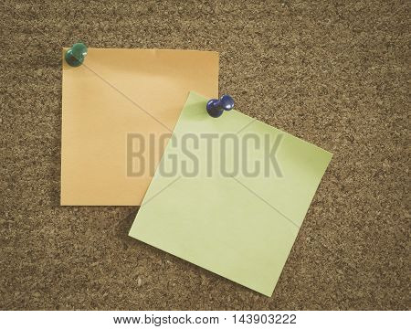 Orange and green sticky notes pinned on brown corkboard vintage effect