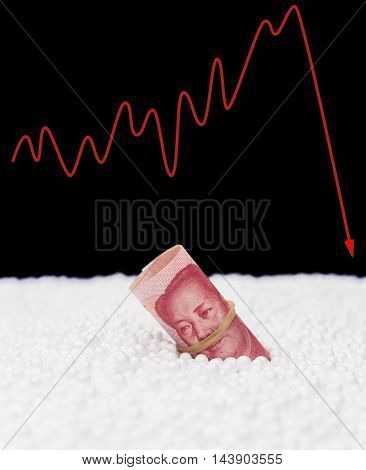 RMB paper currency sink into polystyrene particle and a fluctuation graphic on background monetary concept