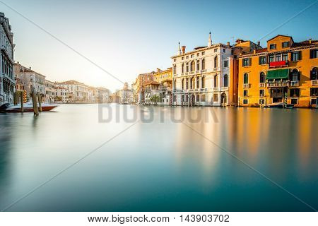 Venice cityscape view on Grand canal with colorful buildings and boats. Long exposure image technic with glossy water
