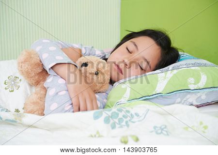 Girl hugging her teddy bear when sleeping