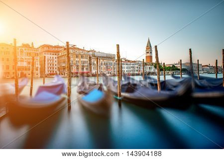 Venice cityscape view on Grand canal with colorful buildings, gondolas and San Marco campanille at the sunset. Long exposure image technic with motion blurred boats and glossy water