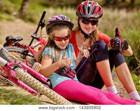 Happy mother and daughter are sitting on road near bicycles. Bicycle racing concept. Bicycle girl wearing helmet show thumb up.