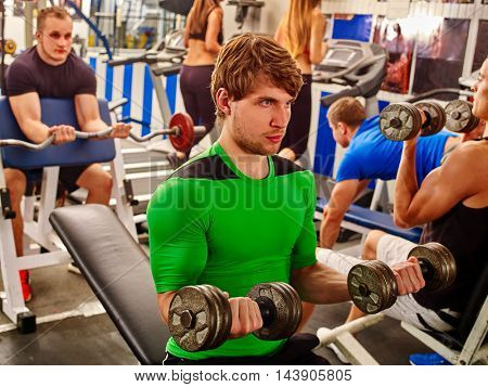 Group of people working with dumbbells his body at gym. Strong man in green with dumbbells on foreground.