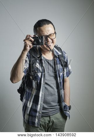 Travel concept. Studio portrait of young man taking a photograph.