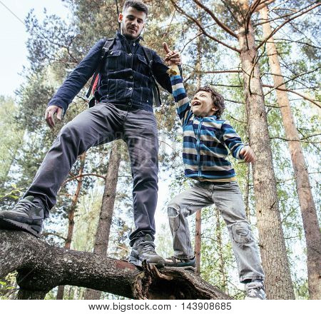 little son with father climbing on tree together in forest, lifestyle people concept, happy smiling family on summer vacations