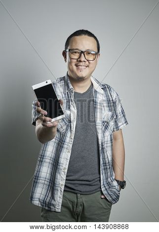 Portrait of a happy asian guy holding a hand phone on plain background