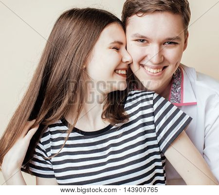 couple of happy smiling teenagers students in love, warm colors having a kiss, lifestyle people concept