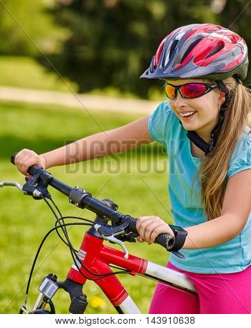 Girl rides bicycle on green grass in park outdoor. Girl in cycling. Cycling is good for good mood. Little cyclist happy. Bicycle girl clings to wheel.