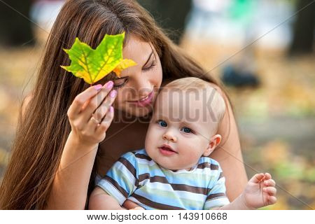 Portrait of happy loving mother and her baby outdoors in park. Leaf fall in fall park.
