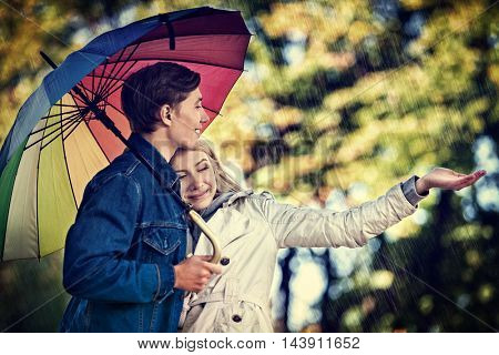Happy young couple embracing under umbrella in autumn day. Love and couple relationships concept and idea. Rain in autumn park.