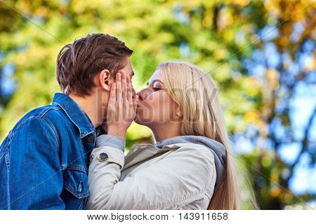 Young couple hugging and kissing in park and looking away. Couple in love walk in autumn park.