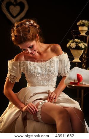 Happy girl in wedding dress sits at table. On table box with wedding ring and burning wedding flower.