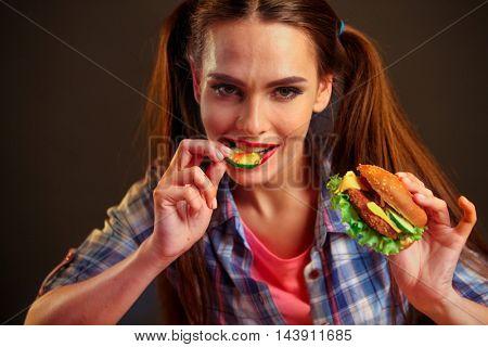 Girl eating hamburger. Girl biting slice of cucumber from hamburger.