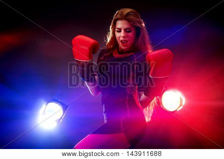 Sports fitness girl with long wearing boxer mitt in multi-colored rays of fitness room.