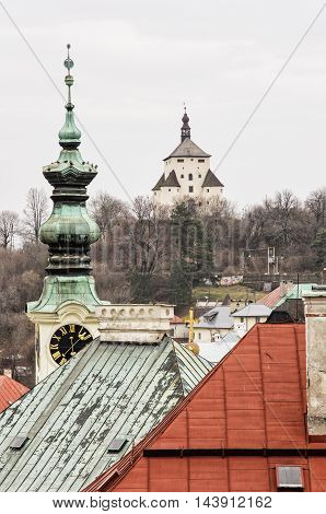 New castle and church tower with clock in Banska Stiavnica Slovak republic. Architectural theme. Old buildings. Travel destination. Cultural heritage. Vertical composition.