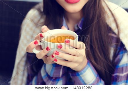 Girl wrapped in a blanket holding a cup of tea close-up in outdoor cafe
