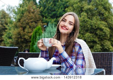 Beautiful smiling girl wrapped in a blanket holding a cup of tea in an outdoor cafe