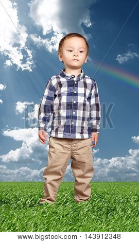 little baby boy outdoors looking for something in green grass