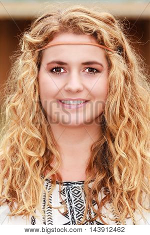 Face portrait of a young blonde woman with curly hair and headband