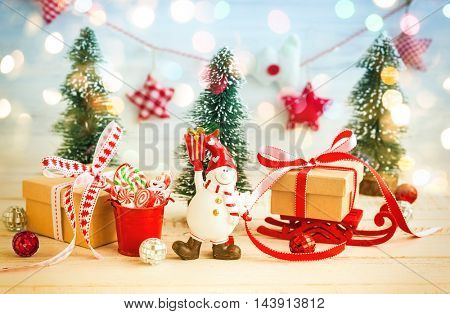 Snowman,gift boxes and decorative Christmas trees on the white wooden background
