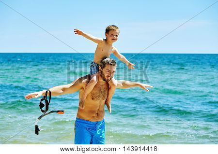 happy father and son playing at sea . Father's day