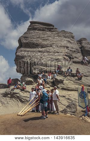 Bucegi Mountains Romania - August 6 2016: People come to contemplate meditate or rest at Sphinx the famous sacred megalith with human face likeness located at 2216 m altitude in Bucegi Mountains.