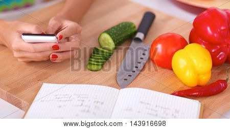 Woman preparing salad in the kitchen, standing