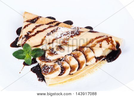 Pancakes stuffed bananas and chocolate on a plate isolated