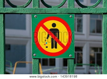 No littering sign in green background on fence